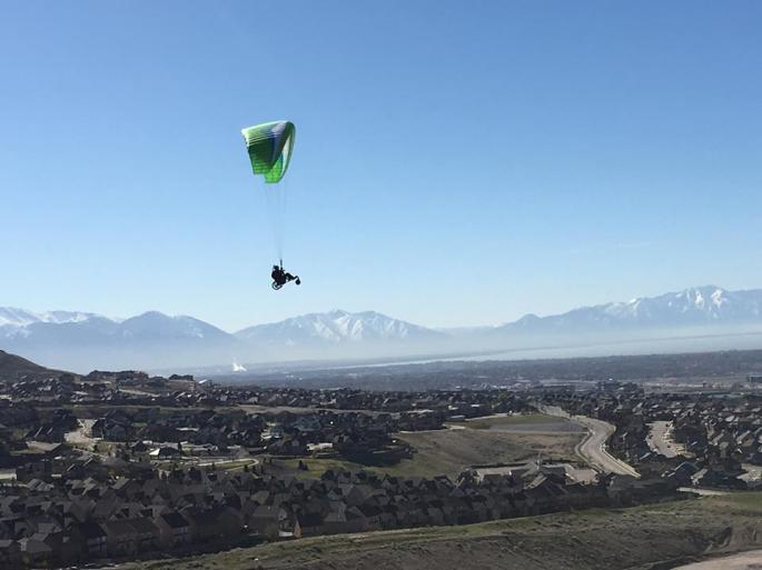 Joe Stone soaring high above the ground with the beautiful mounrains in the background, in his adaptive speed flying equipment.